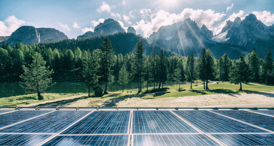Solar panels surrounded by trees and mountains