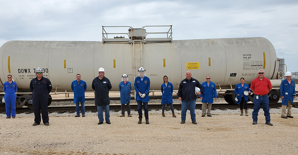 Dow employees at Texas City stand in front of a railcar of IPA